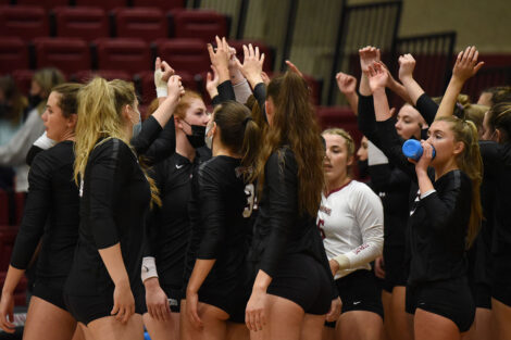 Women's volleyball team high fives each other in a group.